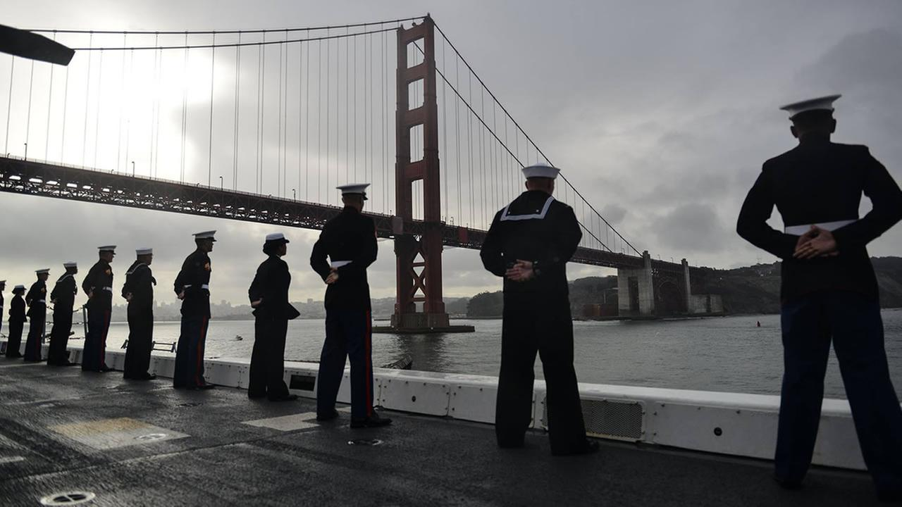 Crew aboard the USS San Diego line the rails as they pass the Golden Gate Bridge in San Francisco on Monday, October 3, 2016.