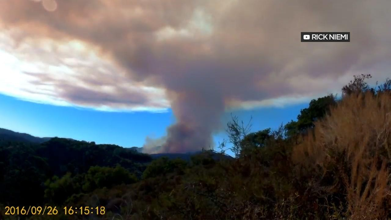 A plume of smoke is seen coming from the Loma Fire burning in the Santa Cruz Mountains in this undated image.