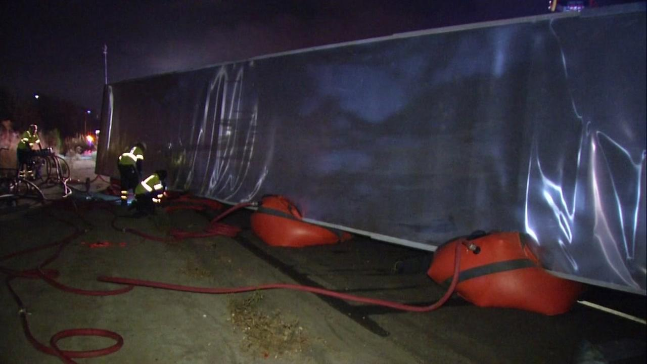 An overturned big-rig on Interstate 580 in Pleasanton, Calif.  is given assistance by a new procedure featuring air bags on Oct. 12, 2016.