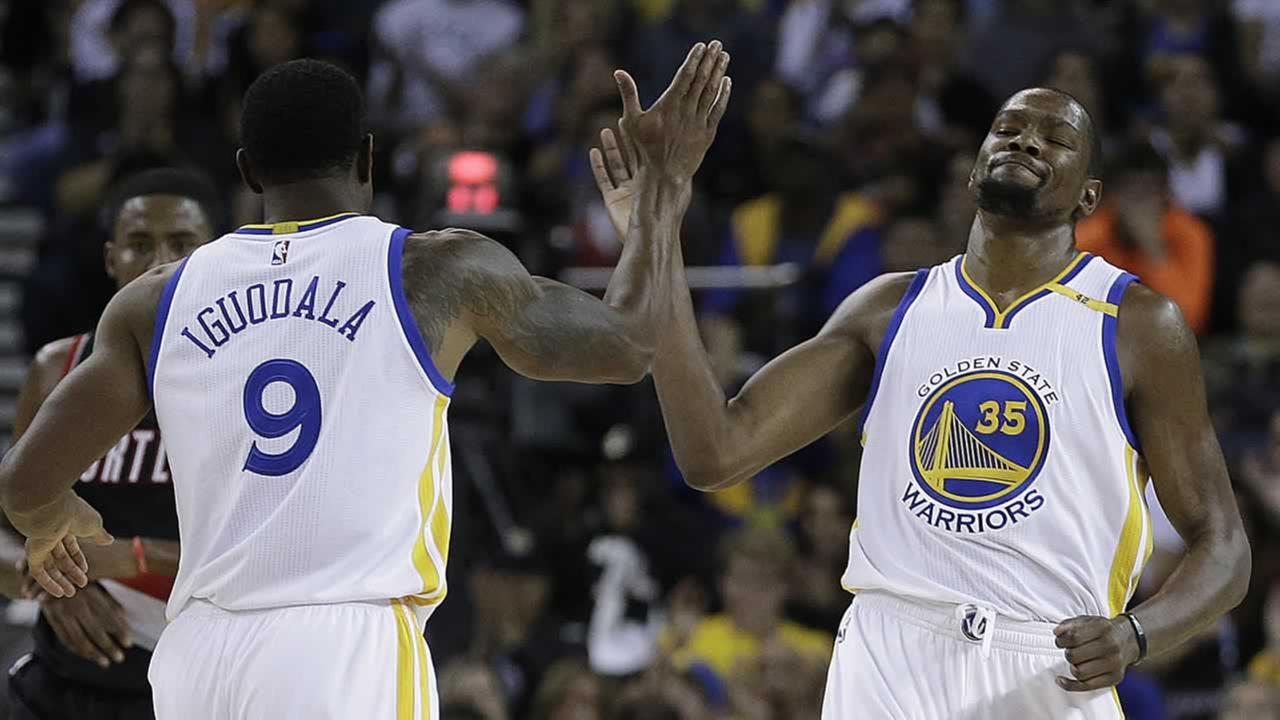 Warriors Kevin Durant, right, is congratulated by Andre Iguodala after scoring during a preseason NBA basketball game Friday, Oct. 21, 2016, in Oakland, Calif.