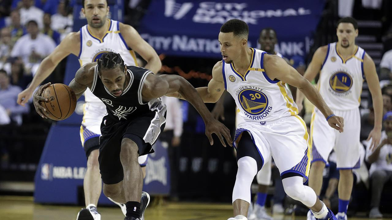 Spurs Kawhi Leonard, left, recovers a loose ball past Warriors Stephen Curry during a home opener on Tuesday, Oct. 25, 2016, in Oakland, Calif. (AP Photo/Ben Margot)