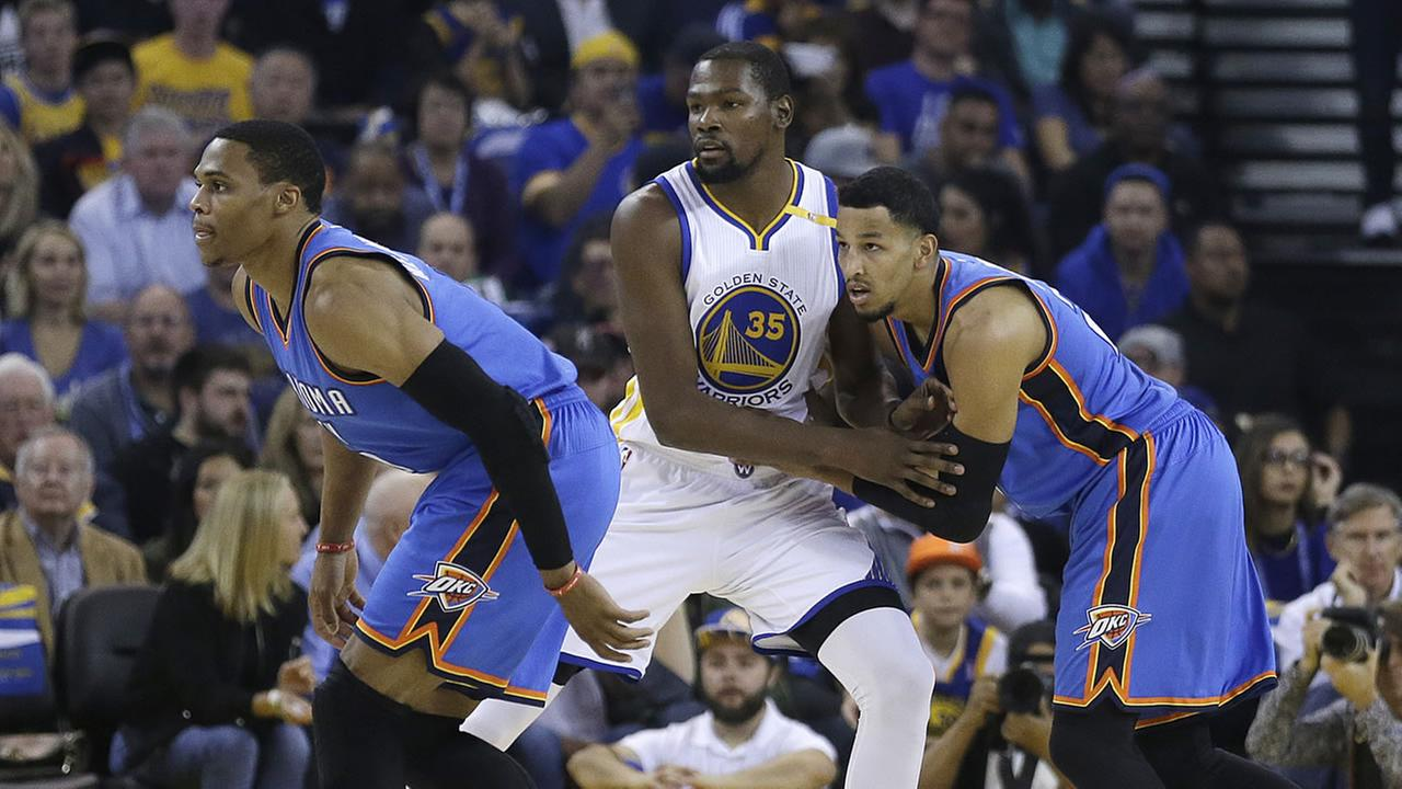 Oklahoma City Thunder guard Russell Westbrook, left, and Andre Roberson, right, uard Golden State Warriors Kevin Durant during an NBA game Nov. 3, 2016, in Oakland, Calif.
