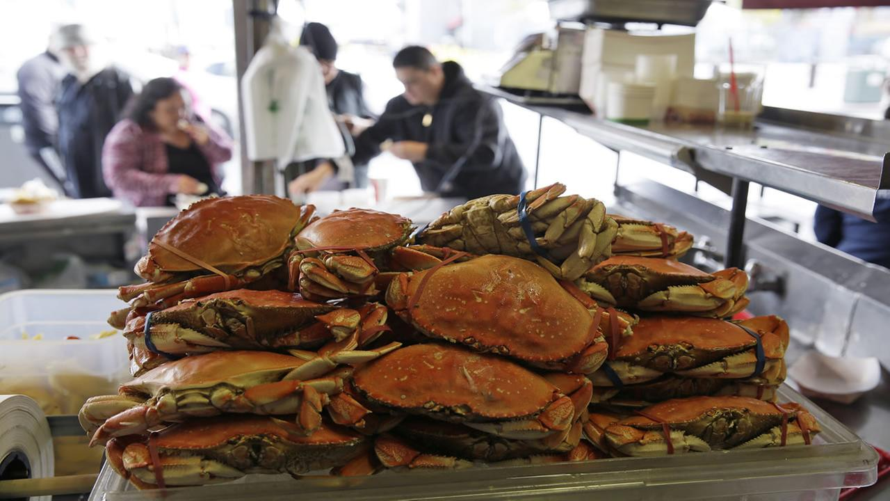 A stack of imported Dungeness crabs are shown for sale as people eat them in the background at Fishermans Wharf Tuesday, Dec. 22, 2015, in San Francisco