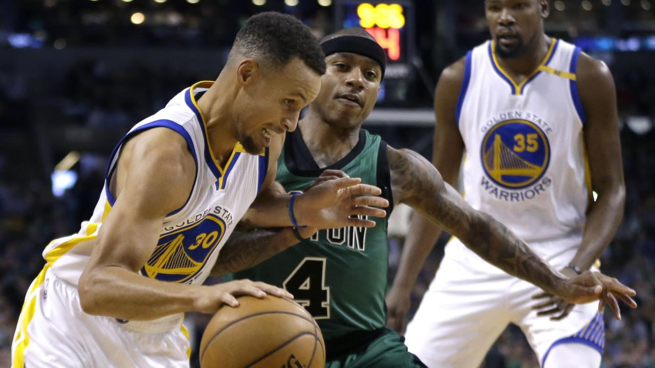 Golden State Warriors guard Stephen Curry (30) drives against Boston Celtics guard Isaiah Thomas (4) as Warriors forward Kevin Durant (35) watches Friday, Nov. 18, 2016, in Boston.