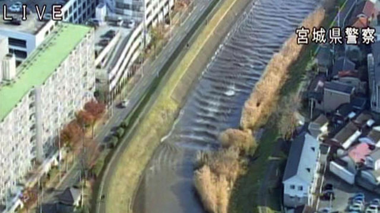 In this image made off a video released by Miyagi Prefectural Police, water rush up Sunaoshi river in Tagajo, Miyagi prefecture Tuesday, Nov. 22, 2016.