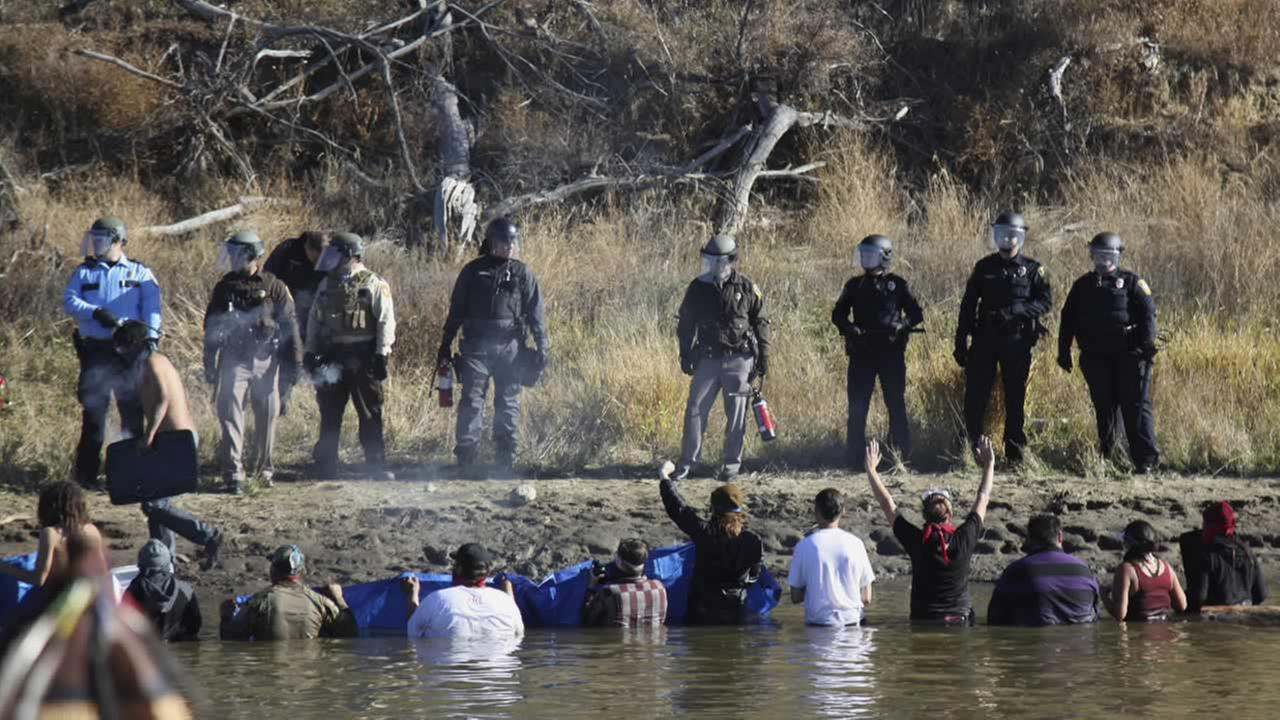 Dakota Access Pipeline protesters wade in cold creek waters confronting local police, as pepper spray wafts over the crowd near Cannon Ball, N.D., Wednesday, Nov. 2, 2016.