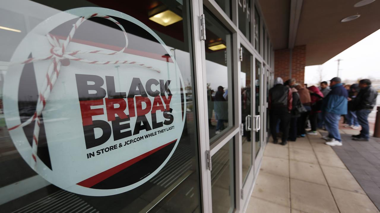 A sign promoting Black Friday specials is displayed in the window of a J.C. Penny store as shoppers queue up at the door for a 3 p.m. opening, Nov. 26, 2015, in Denver, CO.