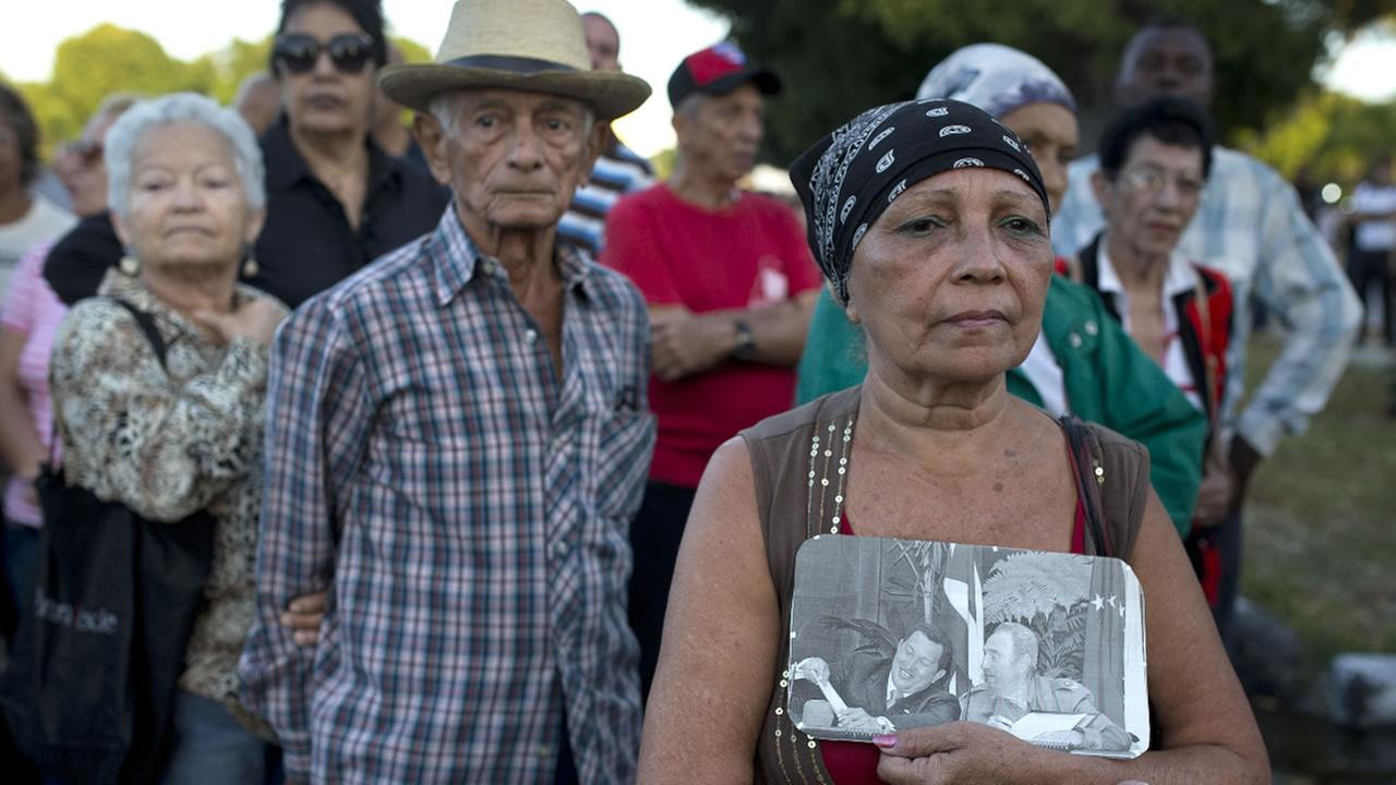 A woman holding a picture of the late Fidel Castro waits in line to enter Revolution Square to render homage to Fidel Castro, in Havana, Cuba, Monday, Nov. 28, 2016.