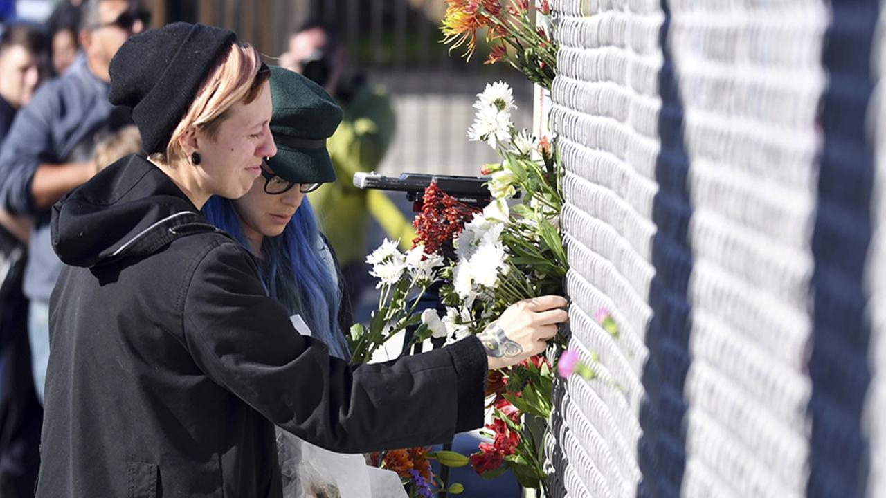 People place flowers near the scene of a warehouse fire Saturday, Dec. 3, 2016, in Oakland, Calif.