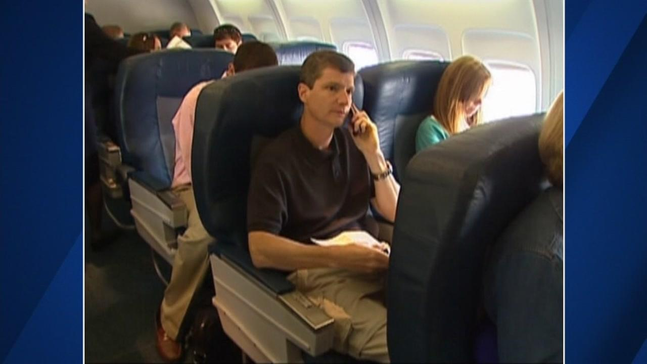 An airplane passenger uses his cellphone in this undated photo.