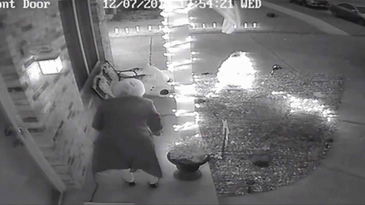 This is an undated image of an elderly woman taking packages from a porch.