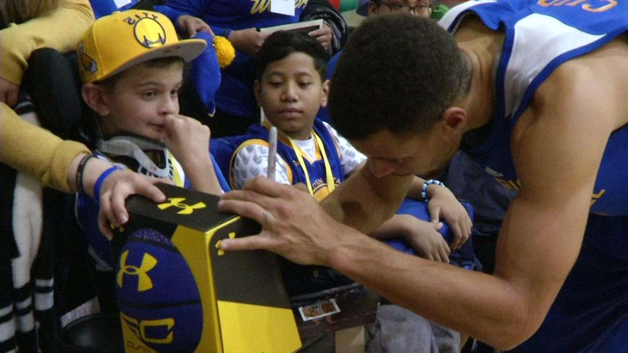 Stephen Curry signs gifts for Make-A-Wish children on Dec. 15, 2016.
