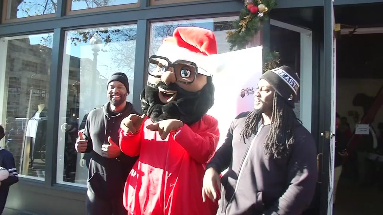 Barron Davis and Marshawn Lynch pose with Black Santa at Lynchs Beast Mode store in Oakland, Calif. on Dec. 22, 2016.