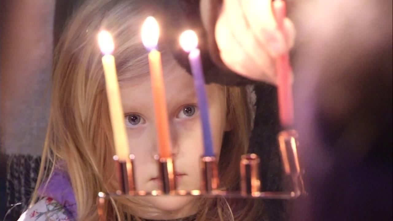 A child looks at a menorah lit on the third day of Hanukkah in San Francisco, Calif. on Dec. 26, 2016.