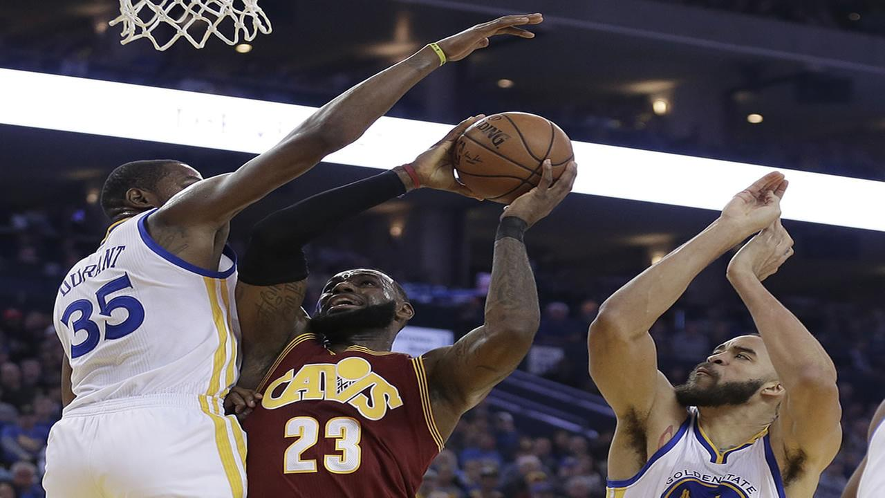 Cleveland Cavaliers LeBron James, center, shoots between Golden State Warriors Kevin Durant (35) and JaVale McGee, right in Oakland, Calif. on Jan. 16, 2017.