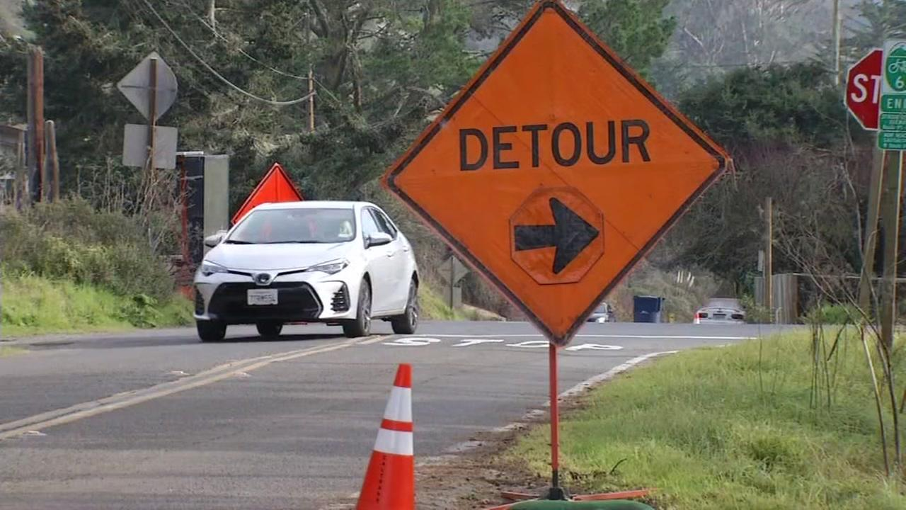 A car drives by a detour sign on Highway 1 in Muir Beach, Calif. on Jan. 17, 2017.
