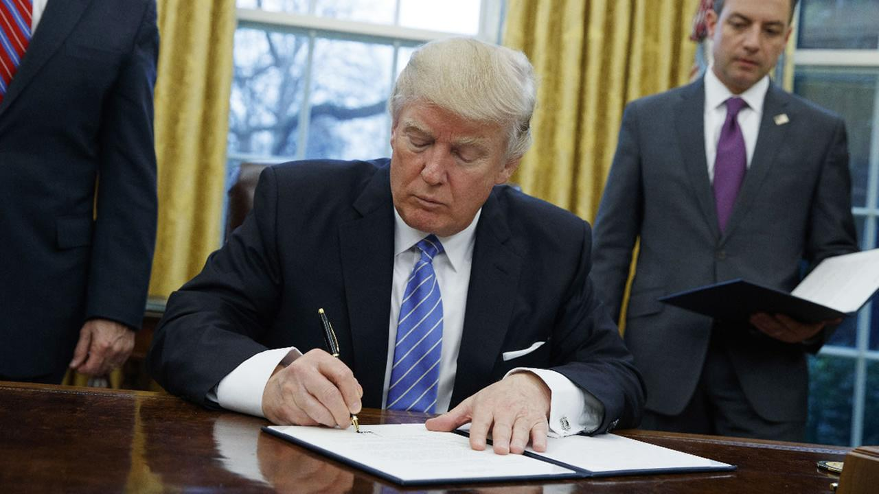 In this Monday, Jan. 23, 2017, file photo, President Donald Trump signs an executive order in the Oval Office of the White House in Washington.