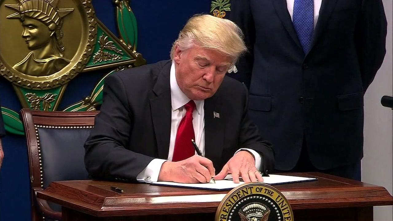 President Donald Trump is seen signing an executive order in this undated image.