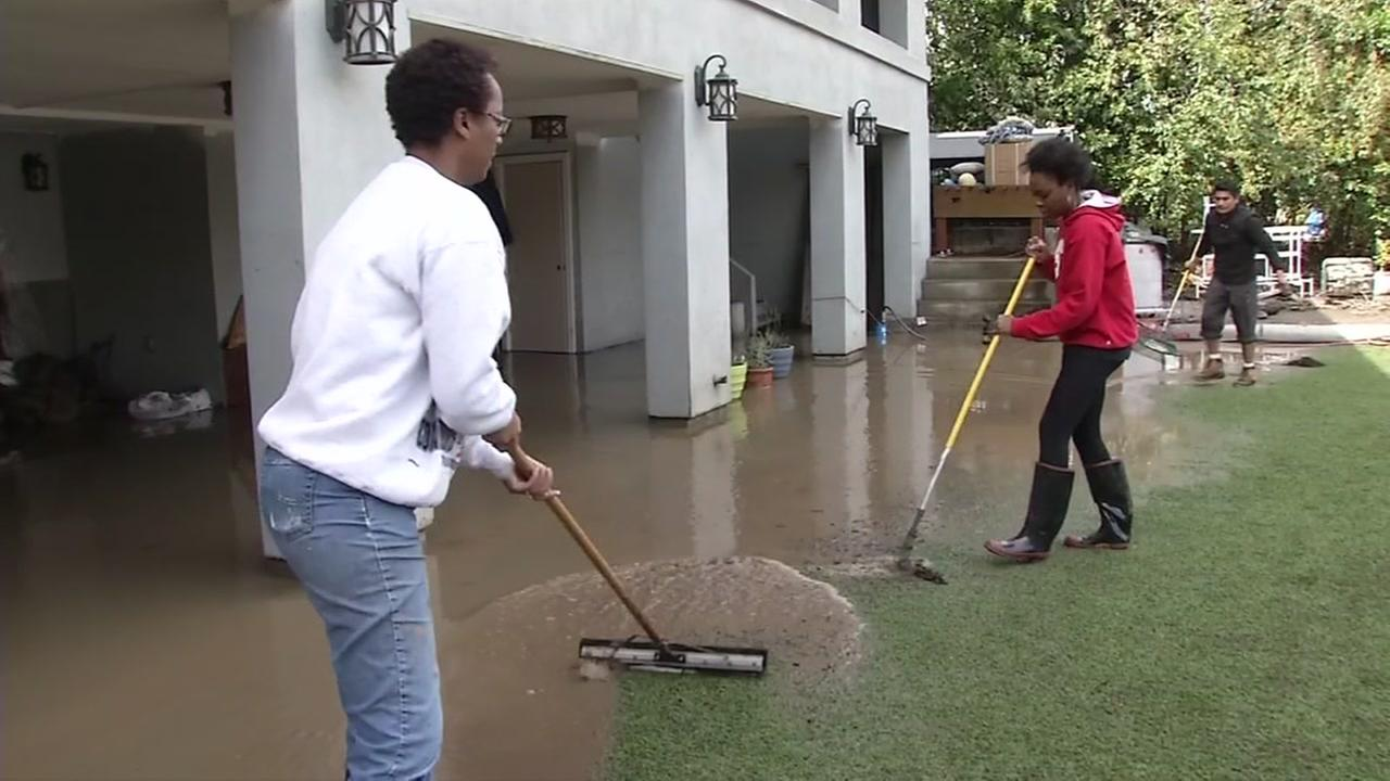 The Powell family sweeps flood water out of their backyard on Wednesday, Feb. 22, 2017 in San Jose, Calif.