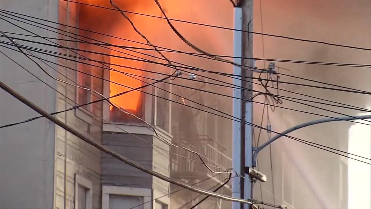 Flames shoot out of an apartment building in West Oakland, Calif. on Monday, March 27, 2017.