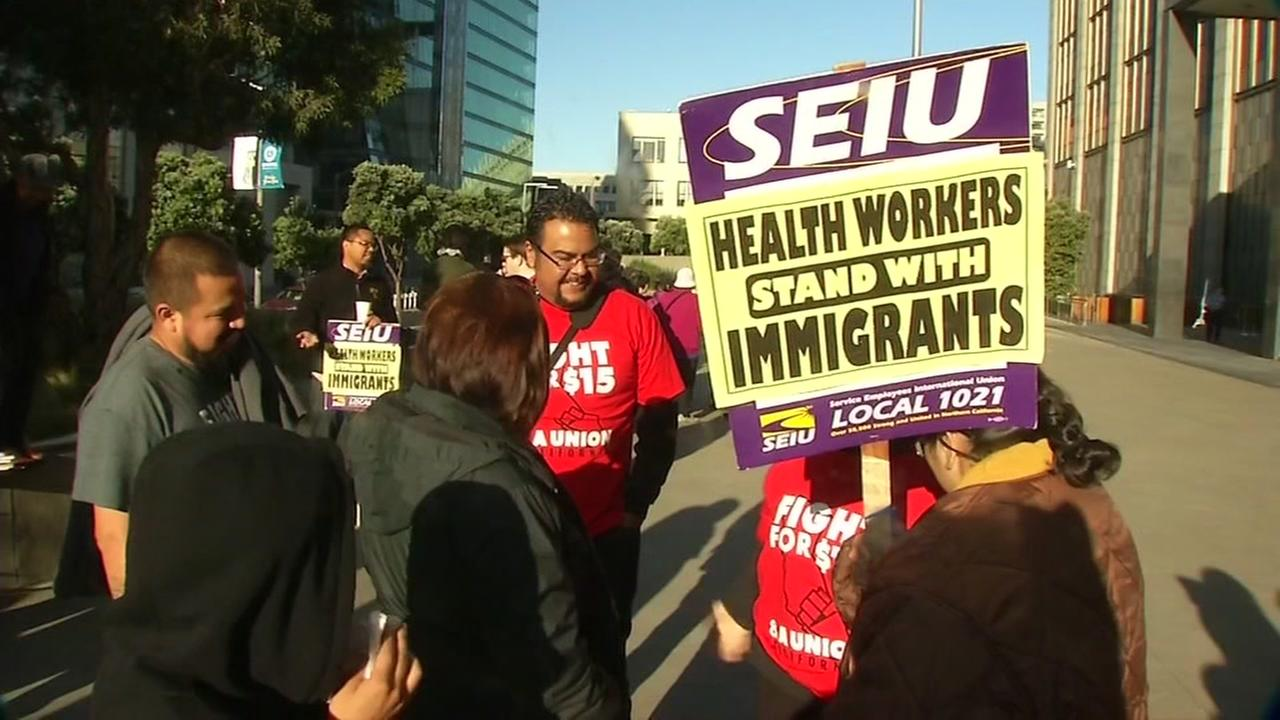Protesters are seen gathering outside a federal courthouse in San Francisco as a judge hears arguments over sanctuary cities on Friday, April 14, 2017.