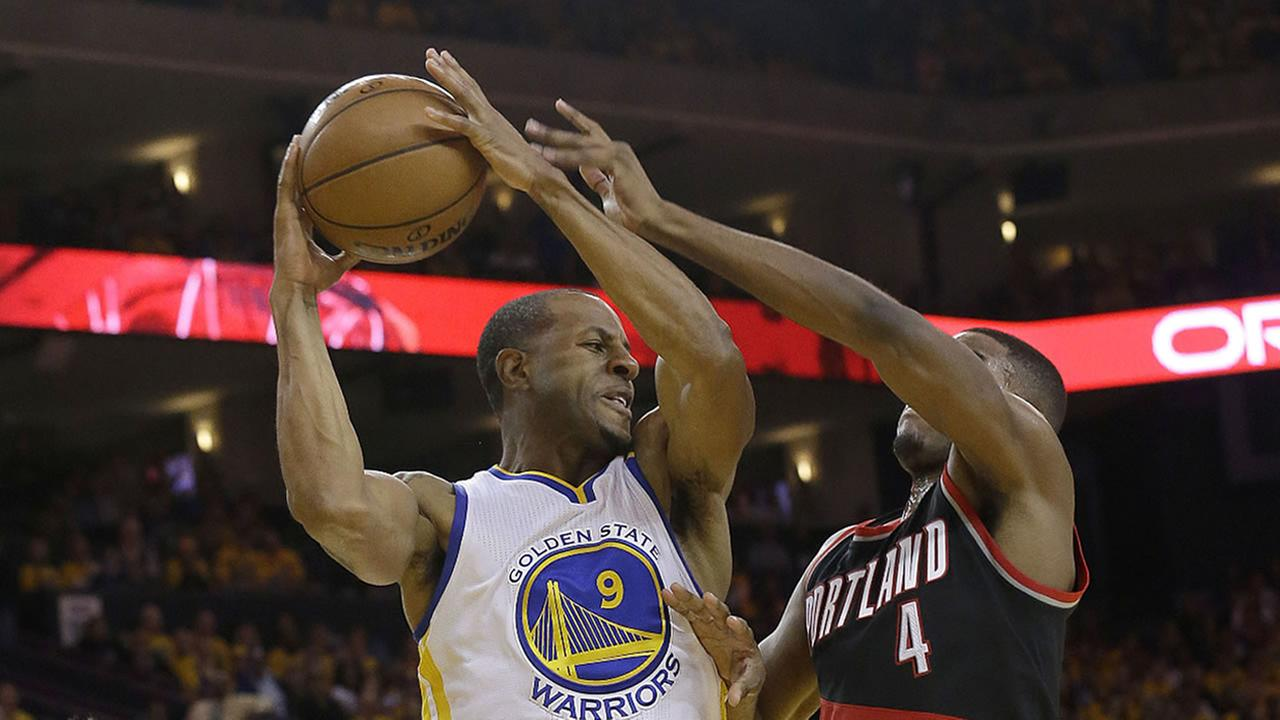Warriors Andre Iguodala passes the ball between Trail Blazers Pat Connaughton during Game 1 of the NBA Playoffs in Oakland, Calif., Sunday, April 16, 2017. (AP Photo/Jeff Chiu)
