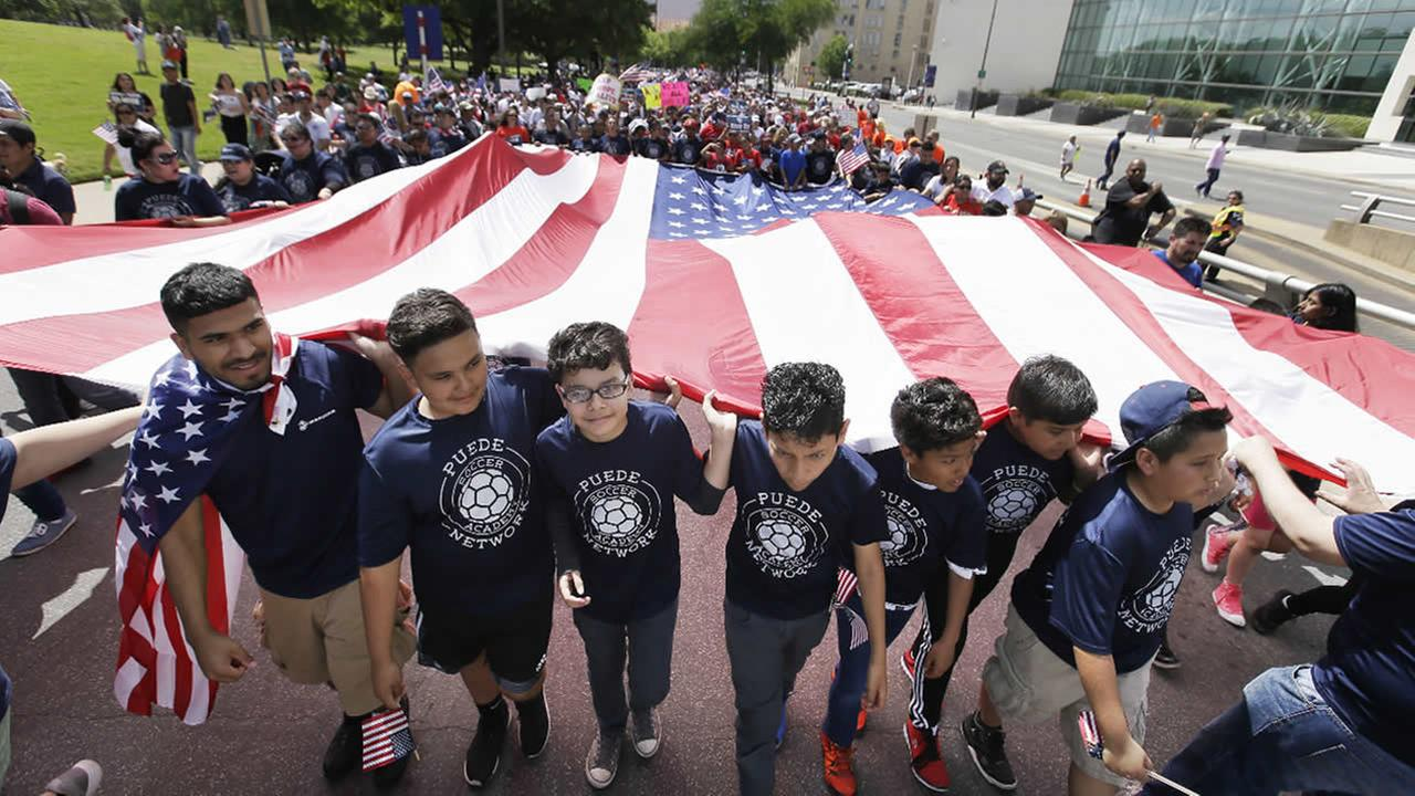 FILE: Youths and adults carry an American flag during a protest march through downtown Dallas, Sunday, April 9, 2017.