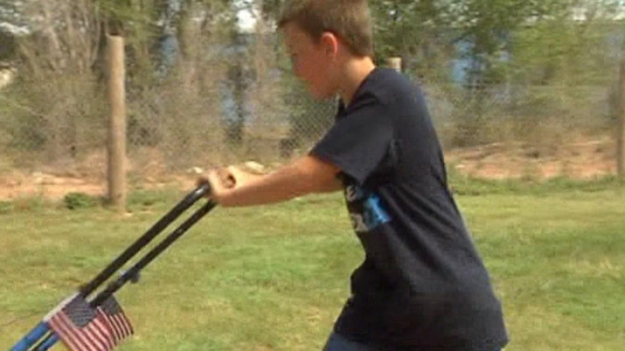 File - Child mows lawn
