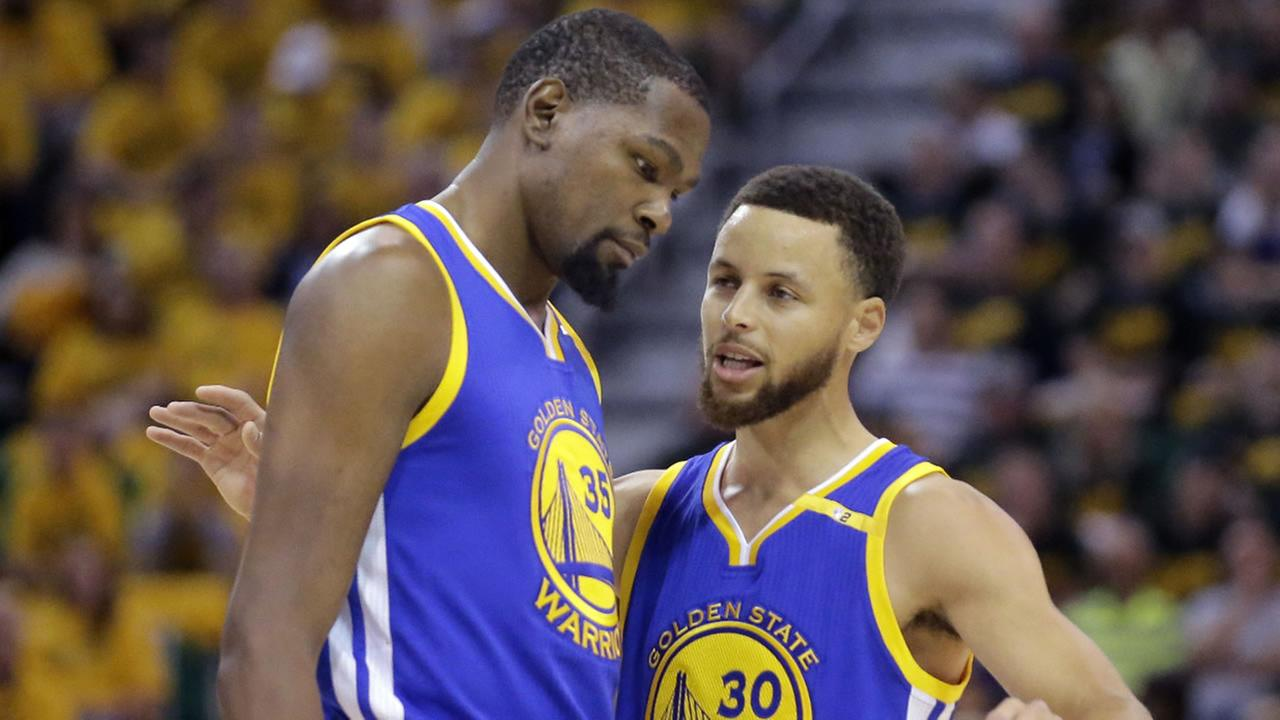 Warriors Stephen Curry (30) and Kevin Durant (35) talk in the first half during Game 3 of the NBA basketball second-round playoff series against the Utah Jazz, Sat., May 6, 2017.