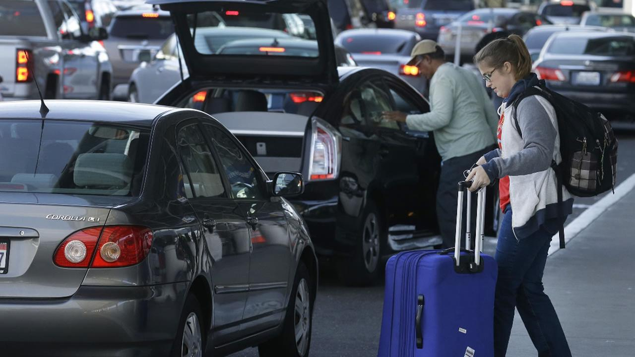 Vehicles jam a roadway at Oakland International airport as travelers wait to be dropped off Thursday, Dec. 17, 2015, in Oakland, Calif.