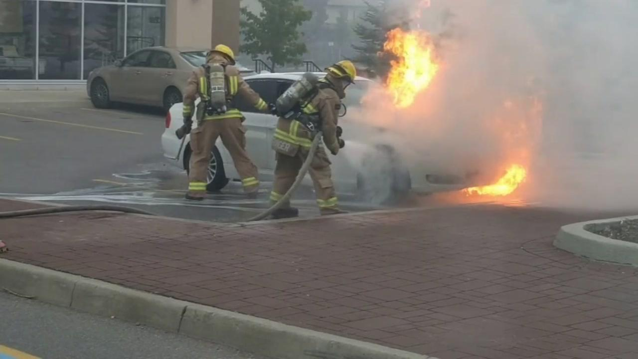 Two firemen put out a BMW fire in this undated image.
