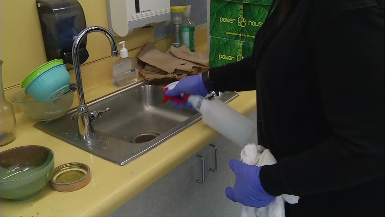 A school employee disinfects a counter at Hacienda Elementary School in San Jose, Calif.