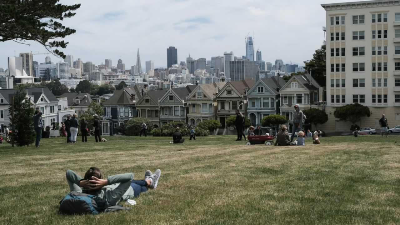 A visitor lounges at Alamo Square Park in San Francisco on Wednesday, May 24, 2017.