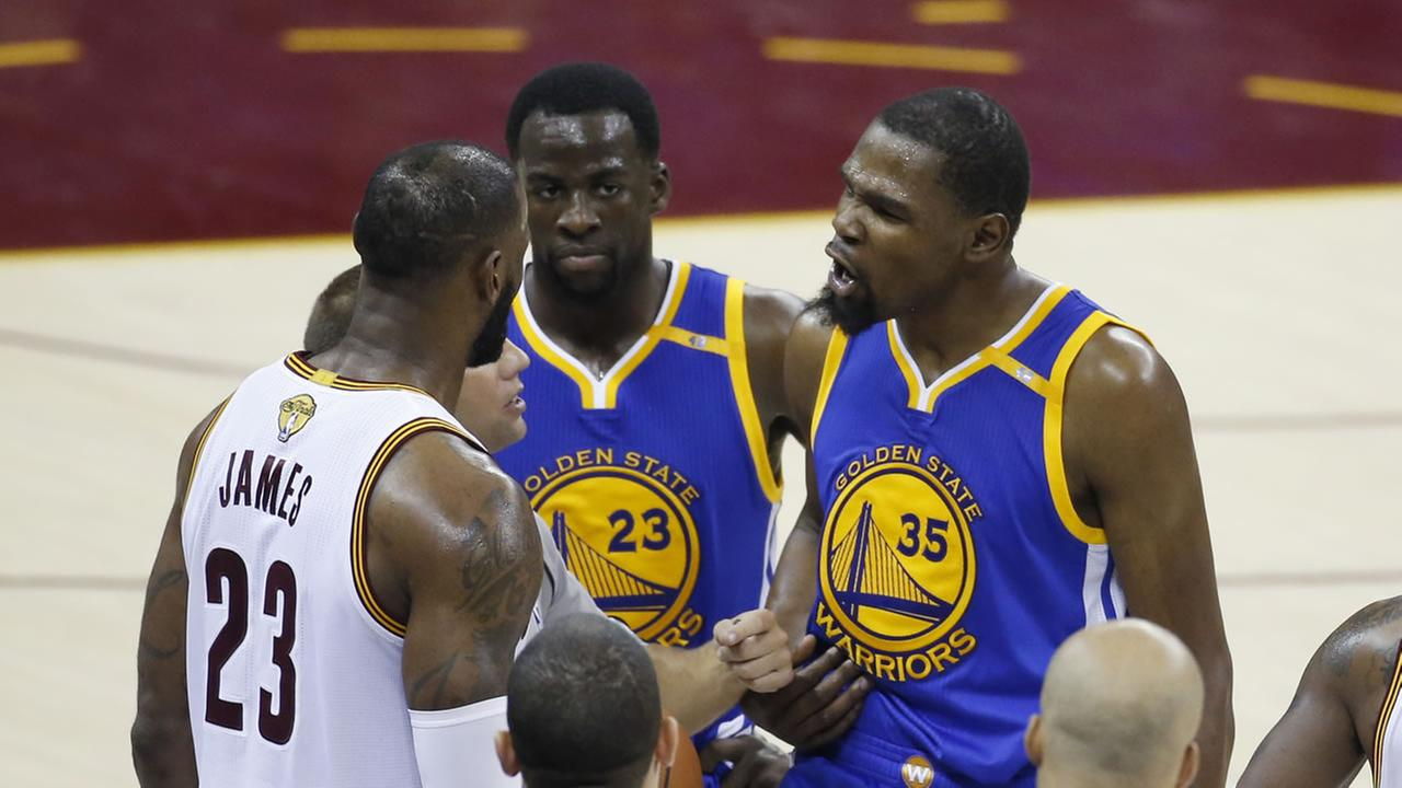 Warriors forward Kevin Durant (35) and Cavaliers forward LeBron James (23) square off on the sidelines of Game 4 of basketballs NBA Finals on June 9, 2017.