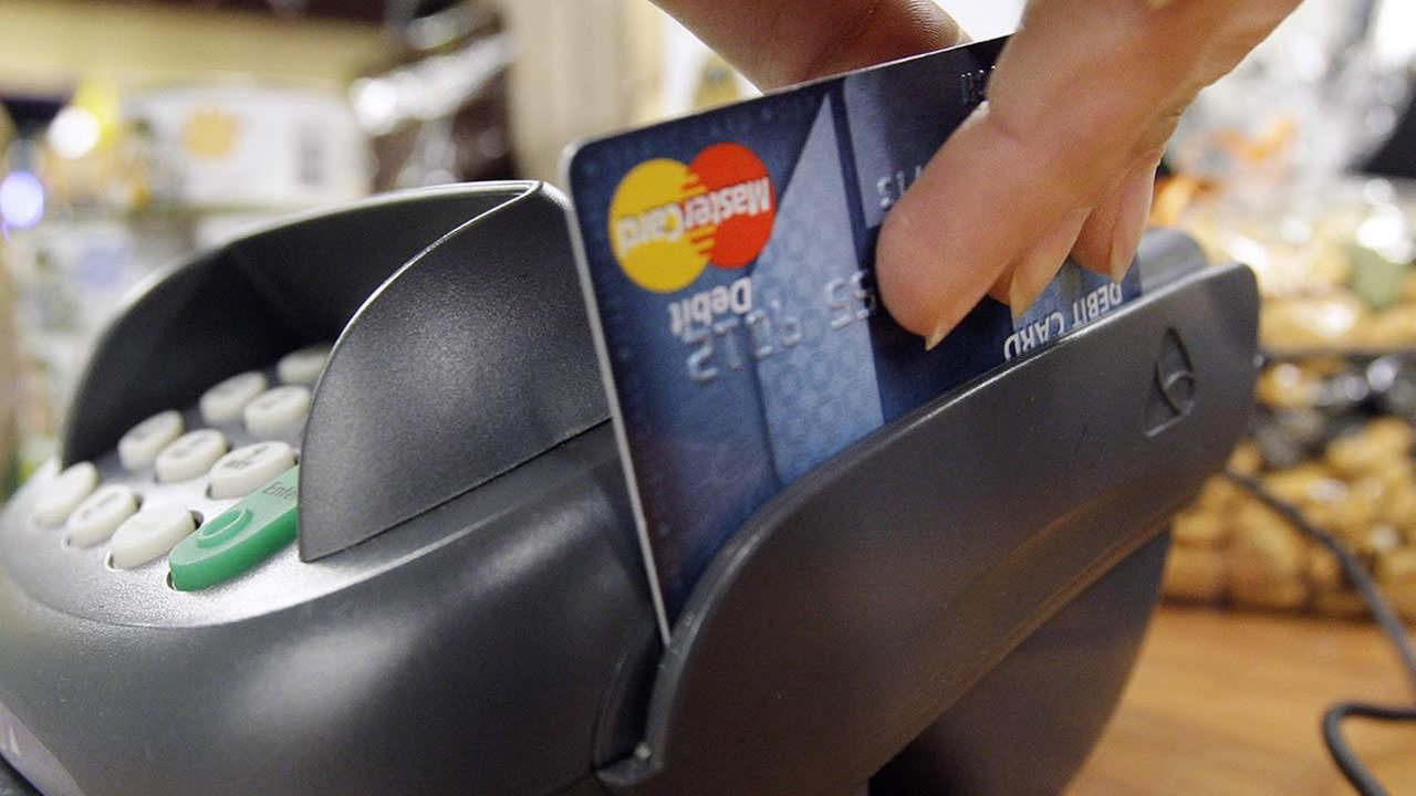 In this Nov. 2, 2009 file photo, a customer swipes a MasterCard debit card through a machine while checking-out at a shop in Seattle. (AP Photo/Elaine Thompson, file)