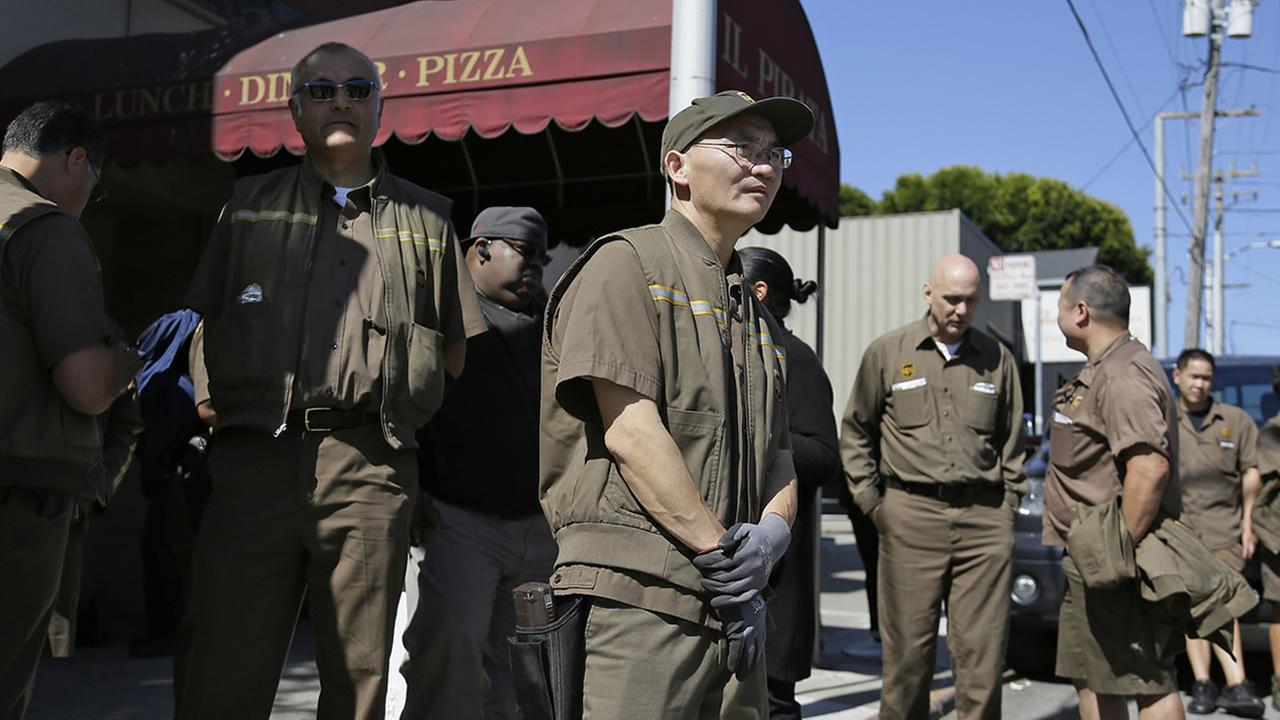 UPS workers gather outside a UPS package delivery warehouse where a shooting took place Wednesday, June 14, 2017, in San Francisco.