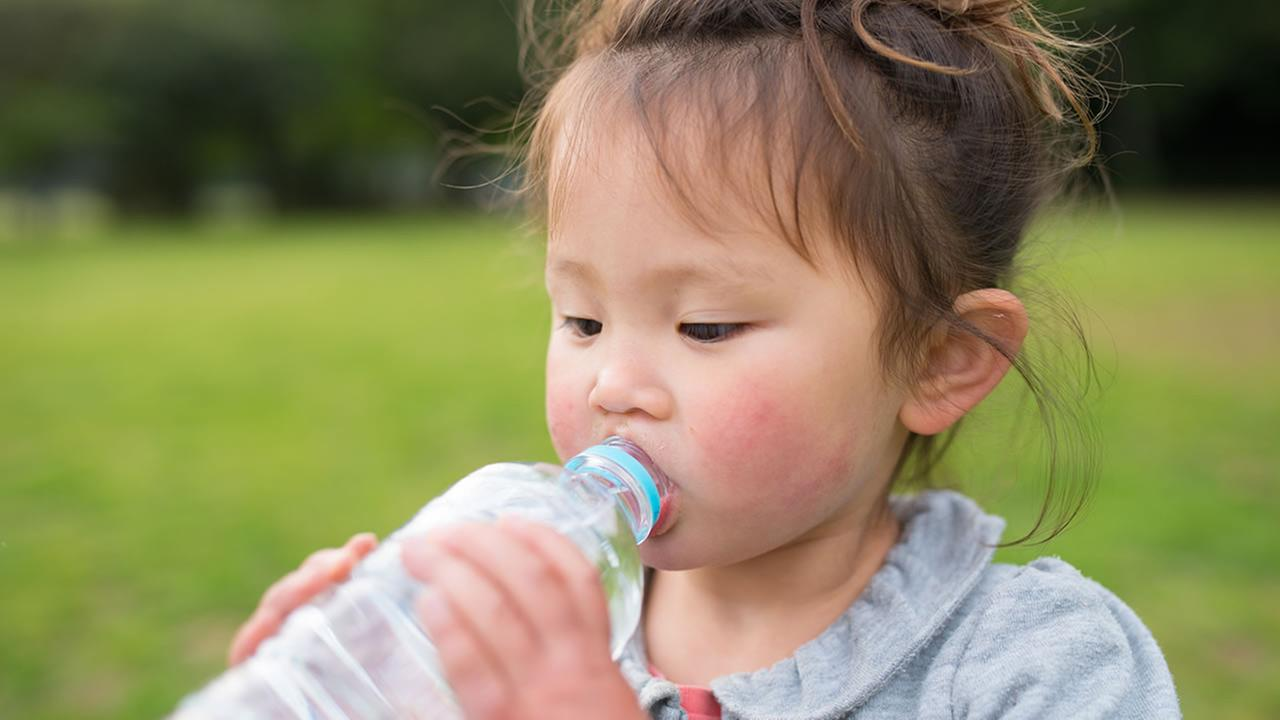 This generic image shows a child drinking water in hot weather.