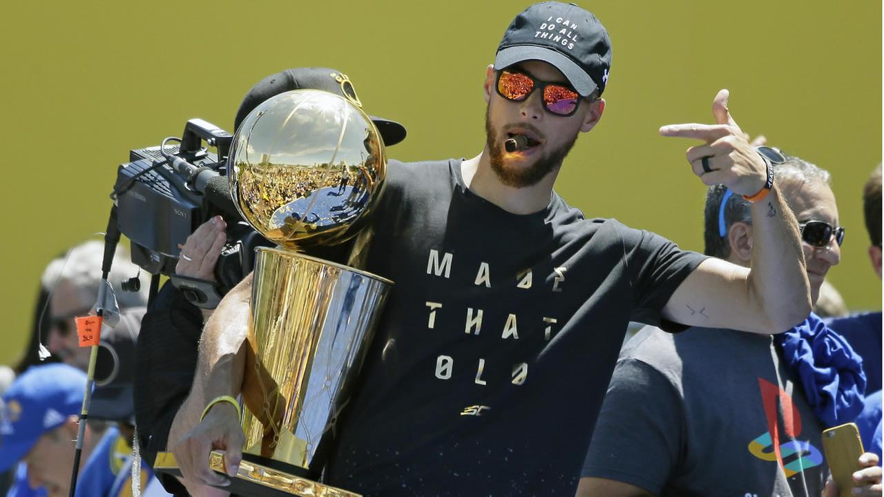 Stephen Curry points to the Larry OBrien trophy during the Golden State Warriors NBA championship rally Thursday, June 15, 2017, in Oakland, Calif. (AP Photo/Eric Risberg)