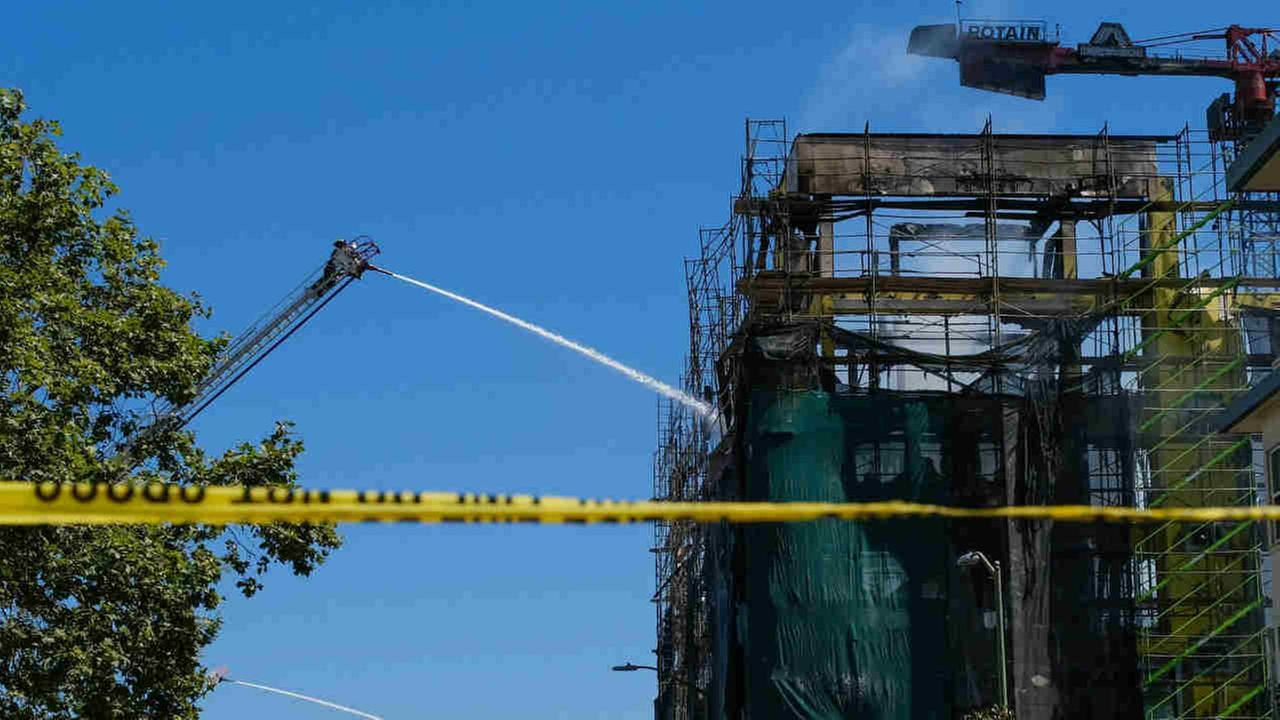 Fire crews are seen working to extinguish a blaze at a construction project in Oakland, Calif. on Friday, July 7, 2017.
