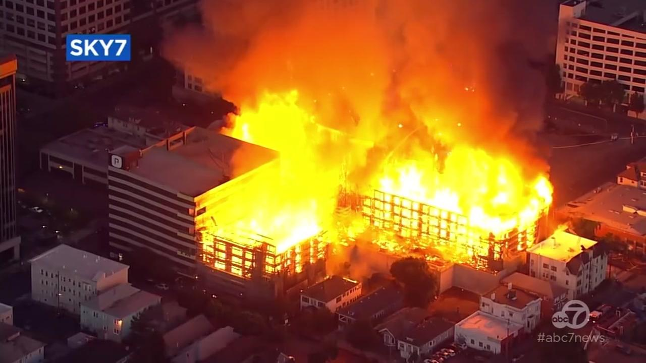 Flames shoot out of an under-construction building in Oakland, Calif. on Friday, July 7, 2017.