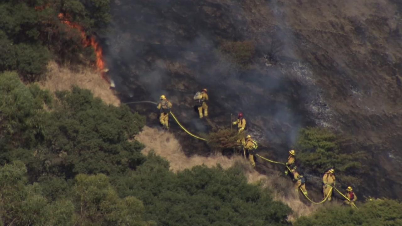 Firefighters scale a hill in San Jose to battle a grass fire on Tuesday, July 11, 2017.