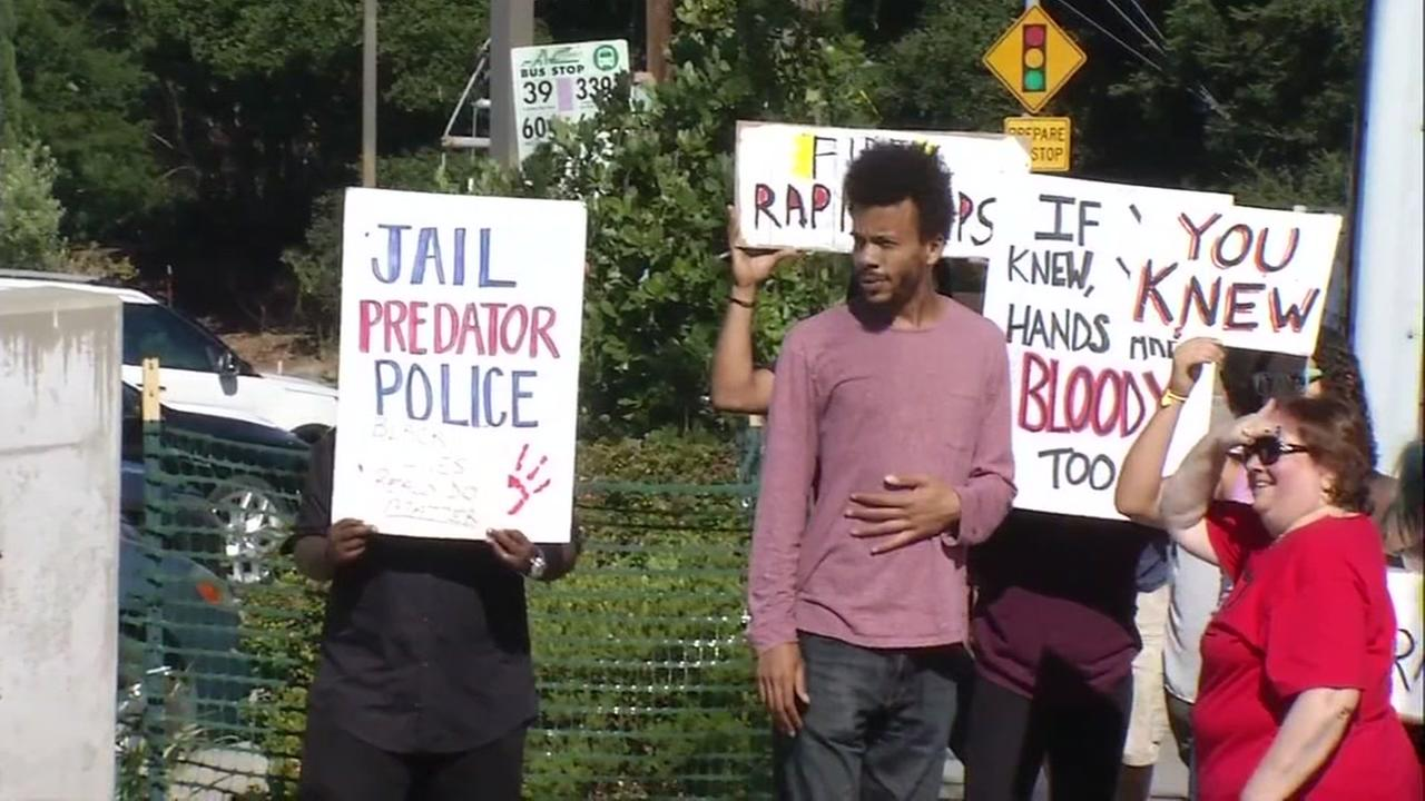 Demonstrators hold signs in Oakland, Calif. on Friday, July 14, 2017 to protest the promotion of two police officials connected to the Bay Area-wide police sex scandal.