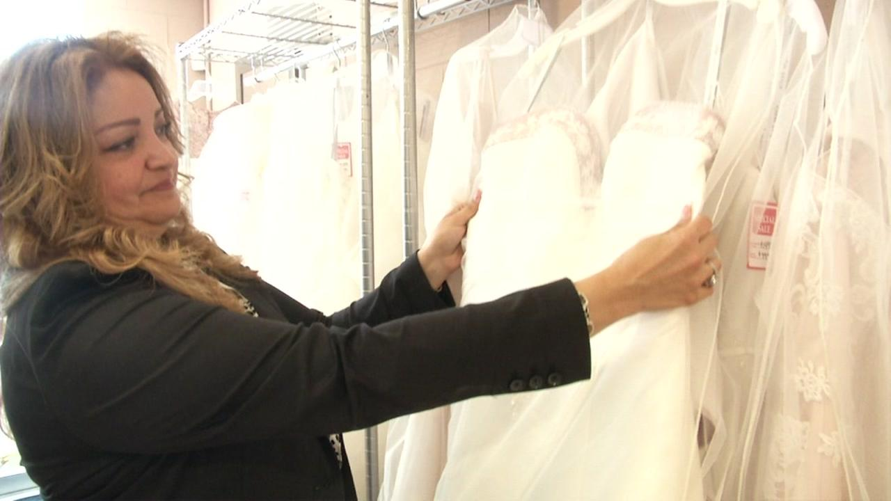 A woman tends to a dress at an Alfred Angelo store in this undated image.