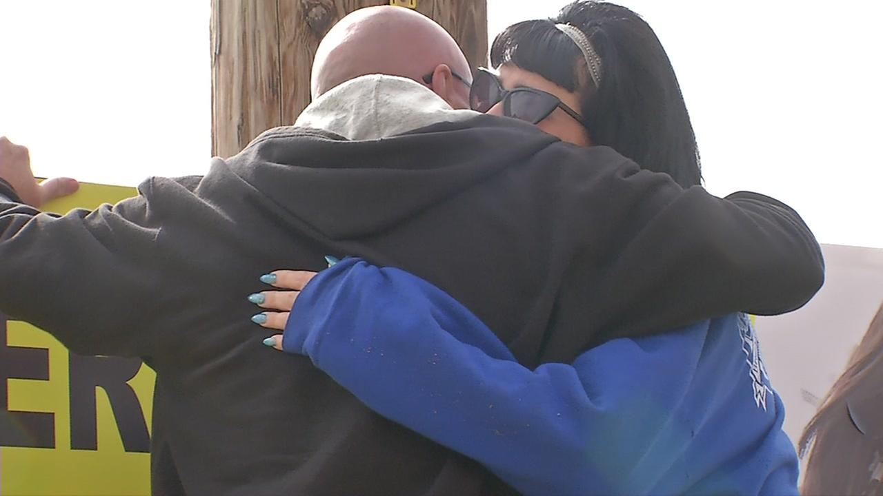 The parents of two young people who were part of tragedy along the San Mateo coastline hug on Friday, July 21, 2017.