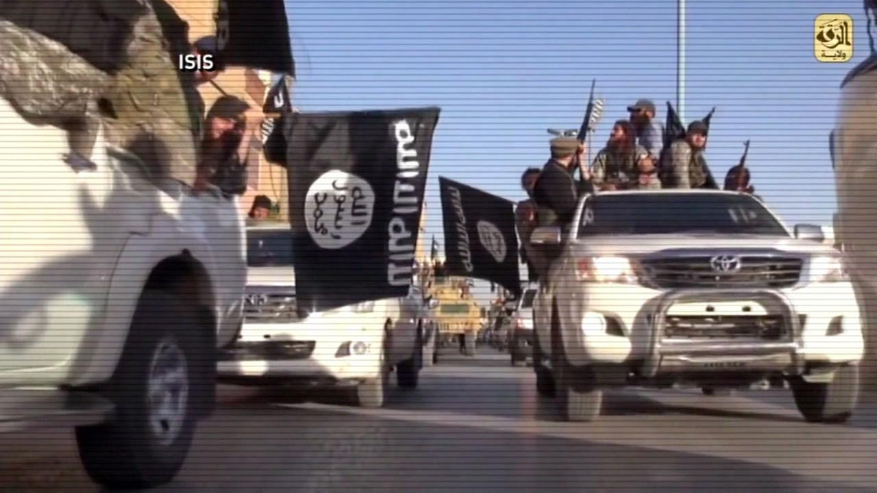 This undated image shows members of ISIS waving flags.