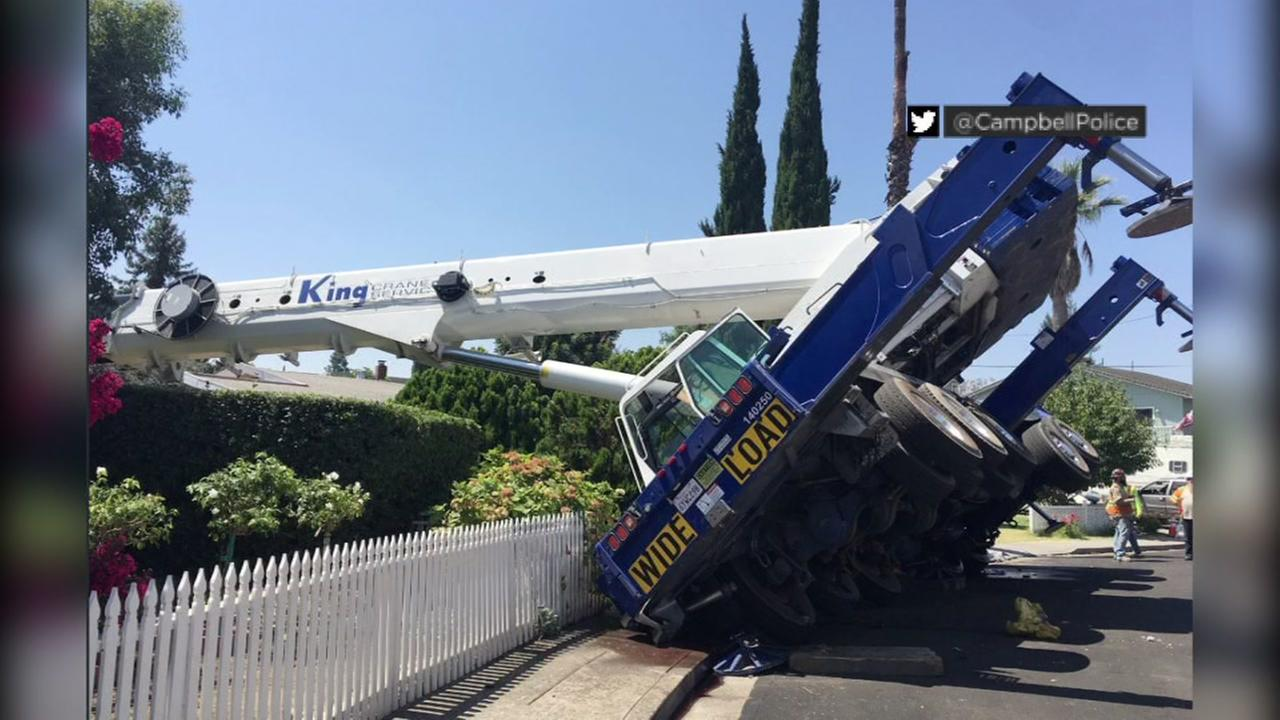 A crane is seen tipped over in Campbell, Calif. after crashing into a home on Tuesday, Aug. 8, 2017.