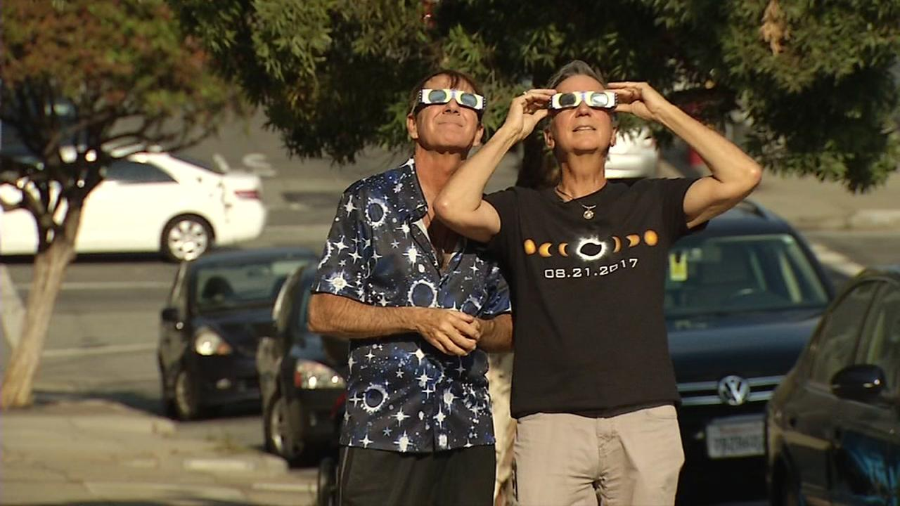 Eclipse chasers Donald Abrams and Clint Werner try out their solar glasses on Friday, August 18, 2017 in San Francisco.