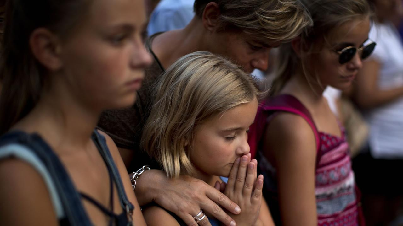 A girl prays next to candles and flowers placed on the ground after a terror attack that killed 14 people and wounded over 120 in Barcelona, Spain, Sunday, Aug. 20, 2017.