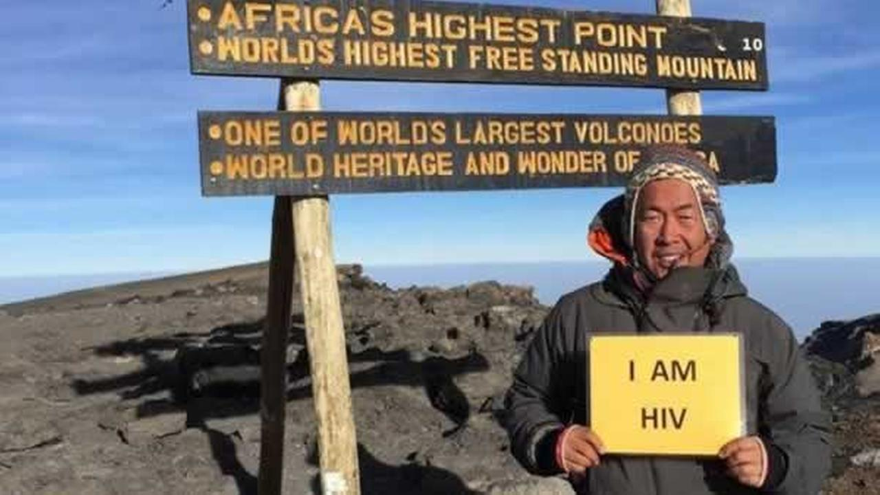 Ferdinand Garcia holds up a sign reading I AM HIV on Mount Kilimanjaro in Tanzania.