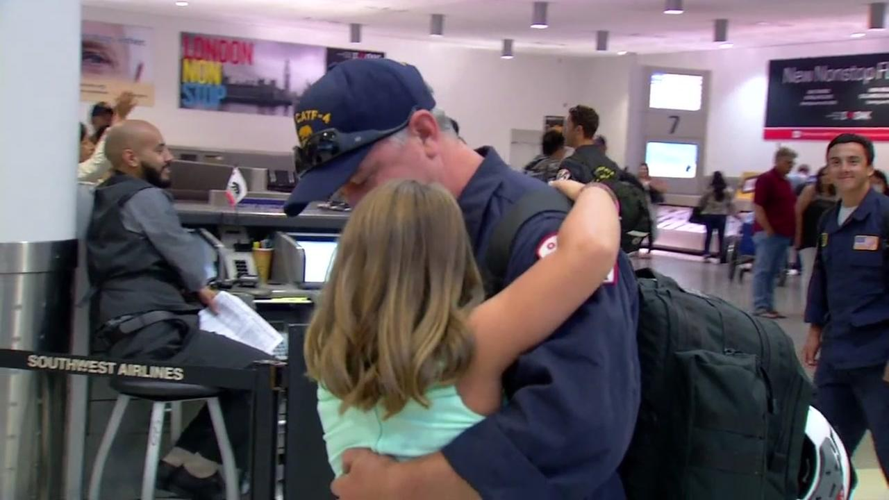 A little girl hugs her father in the Oakland International Airport in Oakland, Calif. after he returned from helping Hurricane Harvey victims in Houston, Texas on Sept. 9, 2017.